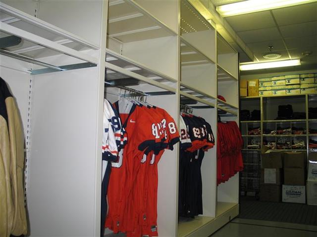 Hanging Jersey Storage on Mobile System Champaign, IL Hanging Jersey Storage Athletic Gear Storage Mobile Shelving Mobile Shelving System Moveable Shelving Education Athletic Equipment Storage Athletic Storage Football Equipment Storage University Of Illinois College Uniforms Team